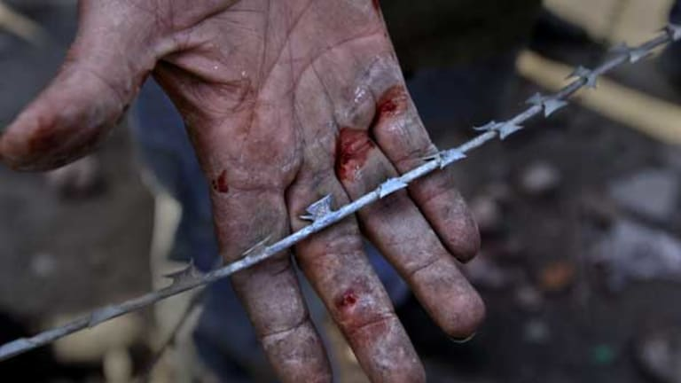 As a show of pride, a man uses his bare hands to remove razor-wire at the barricades set up in Cairo's Tahrir Square.