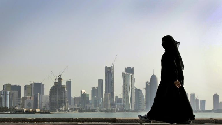 A woman walks in front of the city skyline in Doha, Qatar.