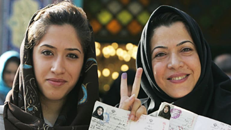 Iranian women show the ink on their fingers and their identification after voting in Tehran yesterday. Women have become a major force in the campaign.