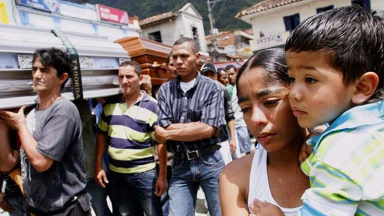Relatives and friends carry coffins of the victims of a coal mine explosion during a collective funeral in Amaga.