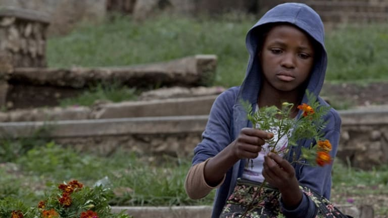 Growth ... Esperanta Michel, 13, prepares fresh flowers to sell to parishioners on Sunday.