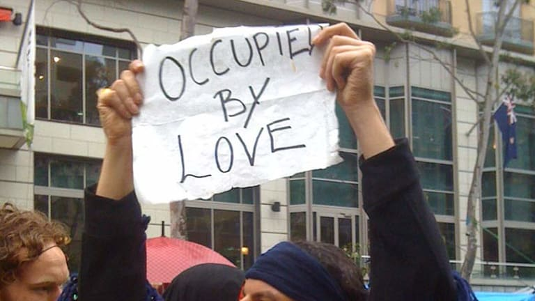 An Occupier holds up a sign. Protesters have called for people to join them at 9am.
