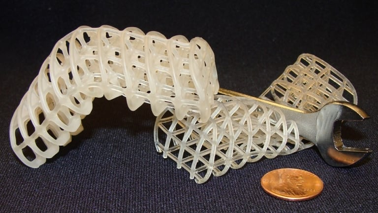 Two 3D-printed soft, flexible scaffolds: the one on the left is maintained in a rigid, bent position via a cooled, rigid wax coating, while the one on the right is uncoated and remains compliant (here, it collapses under a wrench).