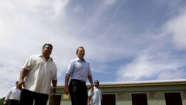 The full tour ... Federal Opposition leader, Tony Abbott takes a tour of the State House camp site, Menen. This site is currently a school but would be turned into a processing facility.