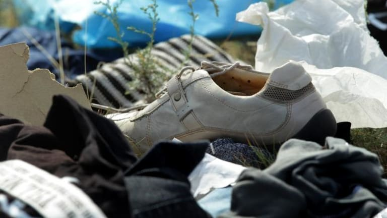 A shoe and other personal items from passengers of flight MH17 at the crash site.