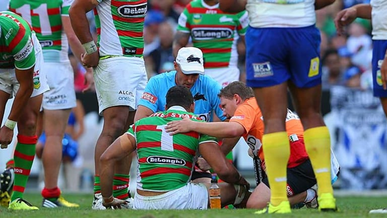 Unhurt: South Sydney star Greg Inglis receives attention after the tackle.