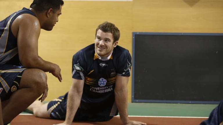 ACT Brumbies player Pat McCabe, centre, chats with a team mate as he warms up before biometric testing in the AIS Indoor Athletics Track.