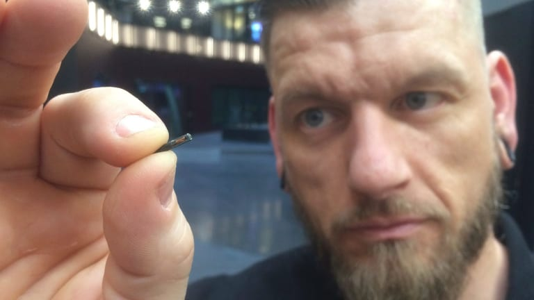 Jowan Osterlund from Biohax Sweden holds a small microchip implant, similar to those implanted in workers at the Epicenter hub in Stockholm.