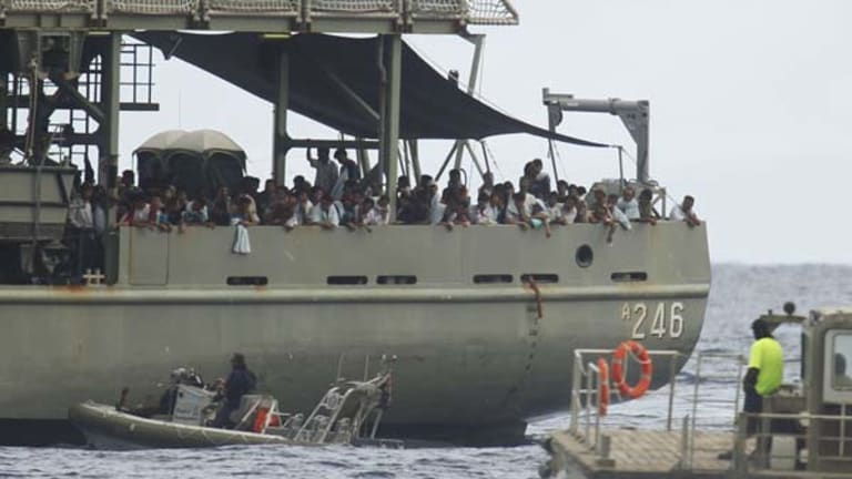 All at sea ... Afghan and Iranian asylum seekers wait aboard HMAS Melville yesterday to be taken to Christmas Island.
