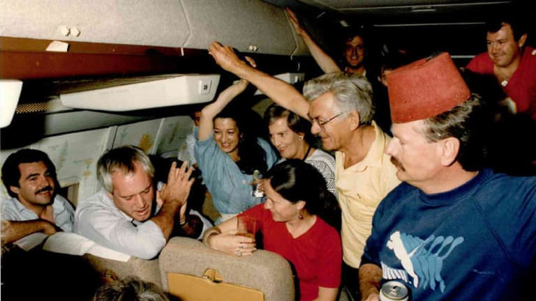 Bob and Hazel Hawke (centre right) with travelling minstrels aboard the old VIP Boeing 707. The late Paul Lyneham (second from left), leads the chorus.