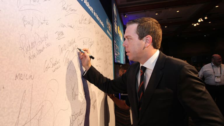 AWU chief Paul Howes signs his name to a pledge to stop Tony Abbott in his tracks at the union's conference in Queensland. Picture: AWU