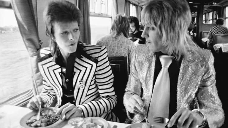 May 14, 1973, Bowie with his intrepid guitarist Mick Ronson (aka Ronno) having a British Rail lunch on the train to Aberdeen at the beginning of his final Ziggy Stardust tour. ''At this time David would not fly anywhere, says photographer Mick Rock. ''Trains and boats were the only travel means they would use. I love the conspiratorial look between them. Like they have a tiger by the tail! Which of course they did. The British music scene would never be the same.''