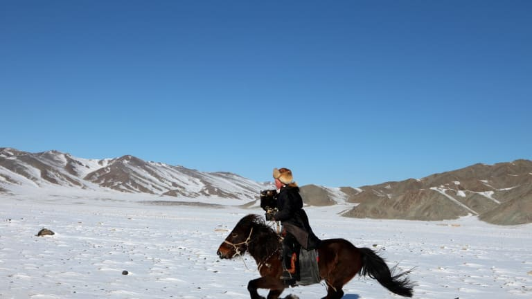 Aisholpan hunting for foxes in the Altai mountains.
