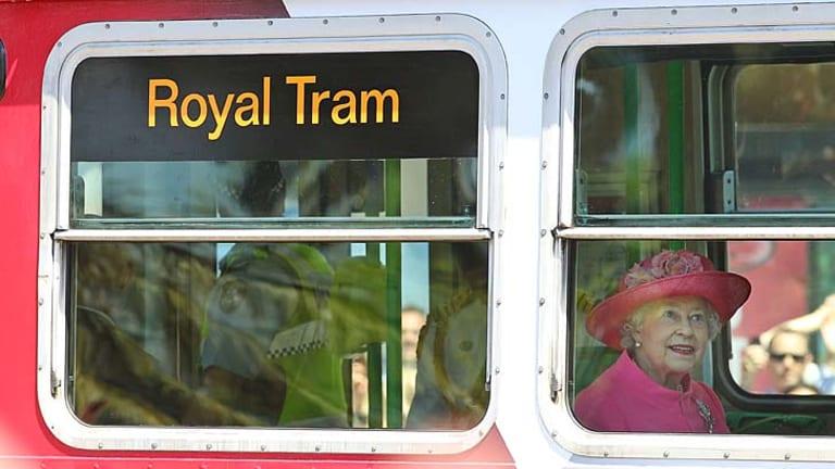 Queen Elizabeth II smiles as she rides on a tram down St Kilda Road.