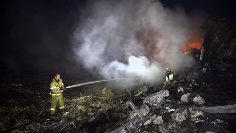 A firefighter douses flames from the wreckage of the Malaysia Airlines plane.