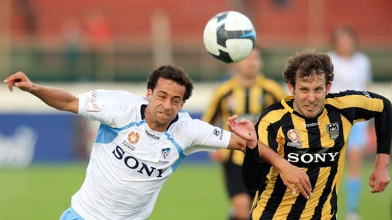 Hard fought win . . . Sydney's Alex Brosque goes into battle for the ball with Jonathan McKain of the Phoenix.