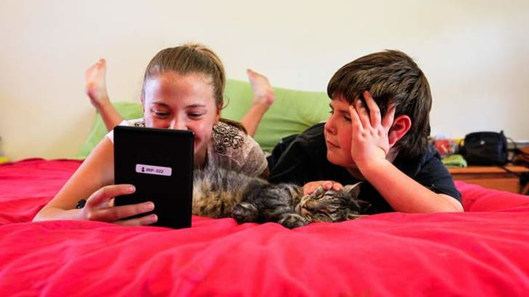 Jade Lewis, age 12, (pictured with 8 year-old brother Darcy) of Richardson received a kindle after improving her reading on the Indigenous Reading Project, a homegrown idea which has helped 100 indigenous children learn to read across Australia.