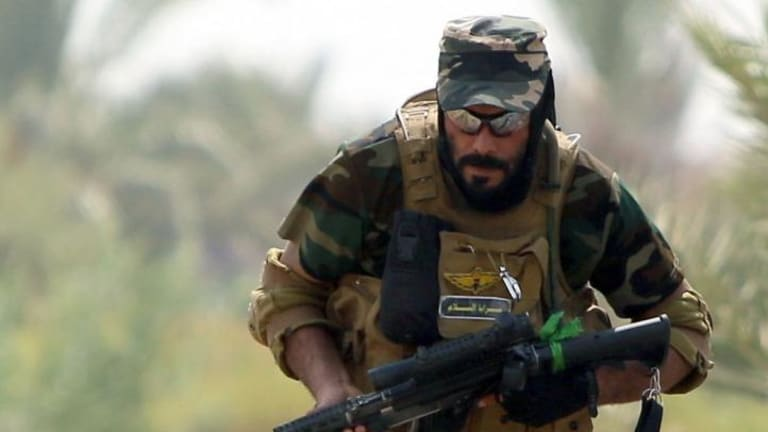 A Shiite Muslim fighter takes up a position against Islamic State fighters.