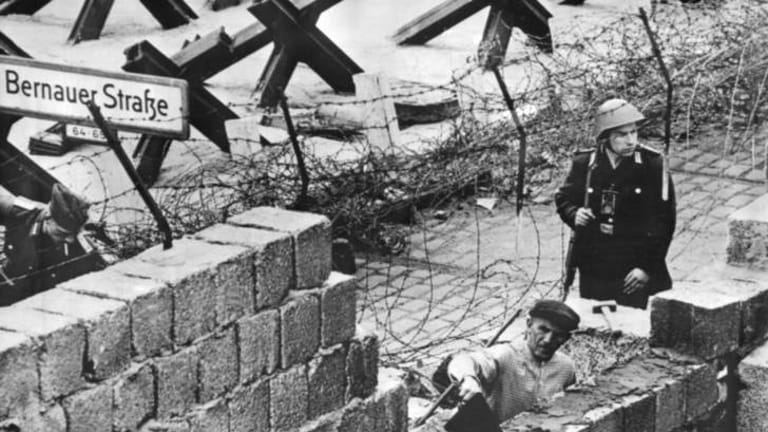 A nation wary of its past: a bricklayer repairs part of the Berlin Wall in 1962.