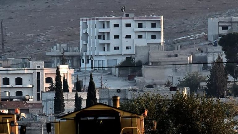 Islamic State militants raise their flag on a building on the eastern edge of Kobane.