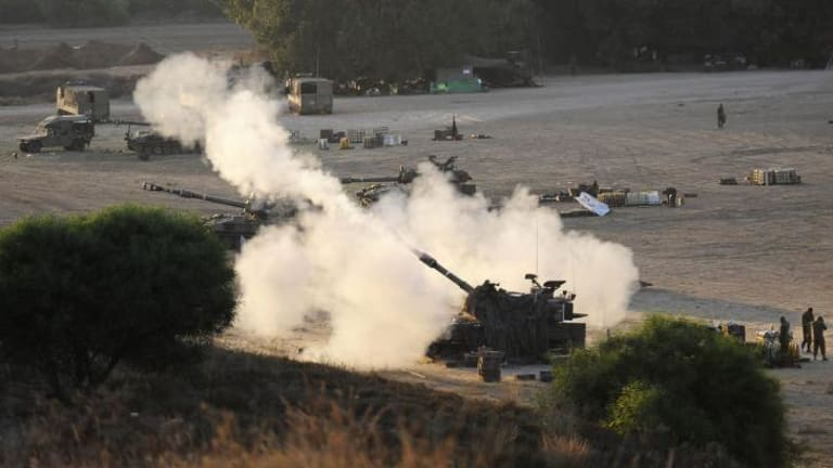 An Israeli tank fires a 155mm shell towards targets in the Gaza Strip on Tuesday. Dozens of Israeli reservists have refused to fight in Gaza.