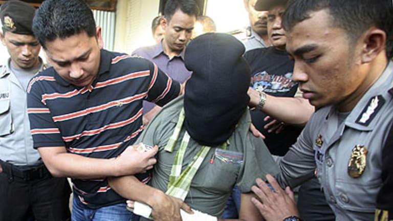 Indonesian police escort a terror suspect in Medan, North Sumatra, on Sunday.