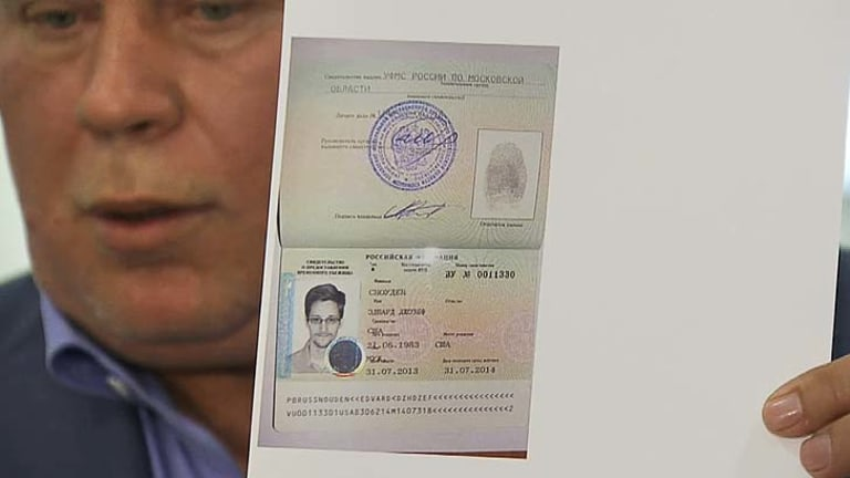 Anatoly Kucherena showing a temporary document to allow Edward Snowden to cross the border into Russia.