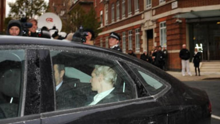 WikiLeaks founder Julian Assange, back to camera,  is driven into Westminster Magistrates Court in London after being arrested on a European Arrest Warrant.