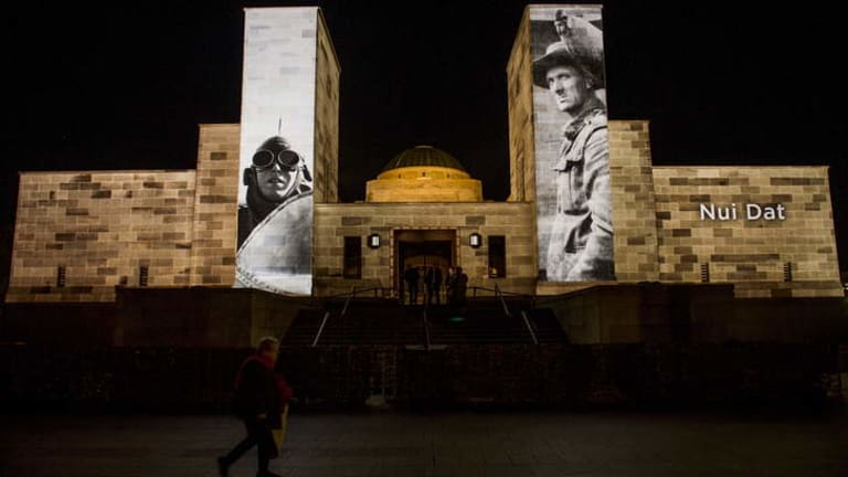 Pictures of service personnel and battles projected onto the war memorial on Anzac Day.