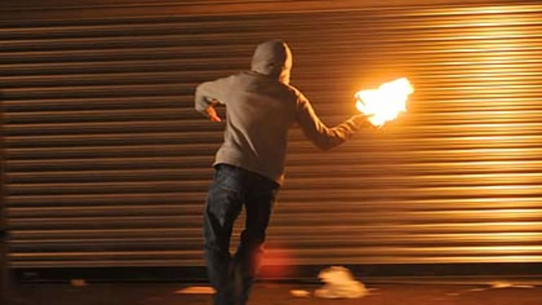 A masked nationalist throws a Molotov cocktail at the police in Belfast.