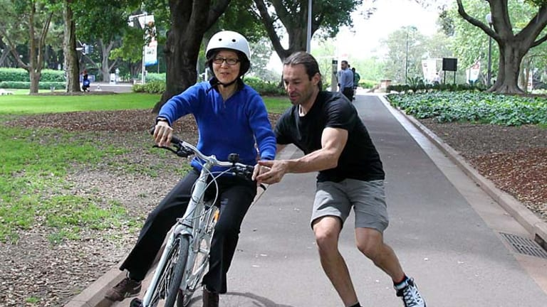 Something she'll never forget… cycling coach George Mihelakis teaches Sian Lian Lee, 56, how to ride a bike as part of National Ride to Work Day.