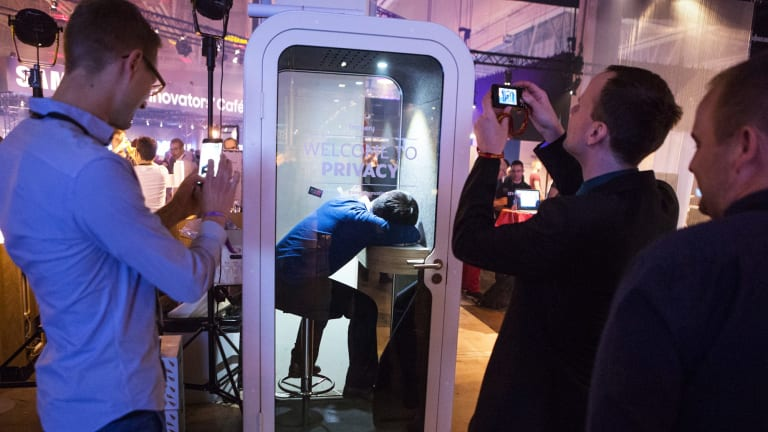 An attendee takes a nap in a privacy booth at Slush 2016.