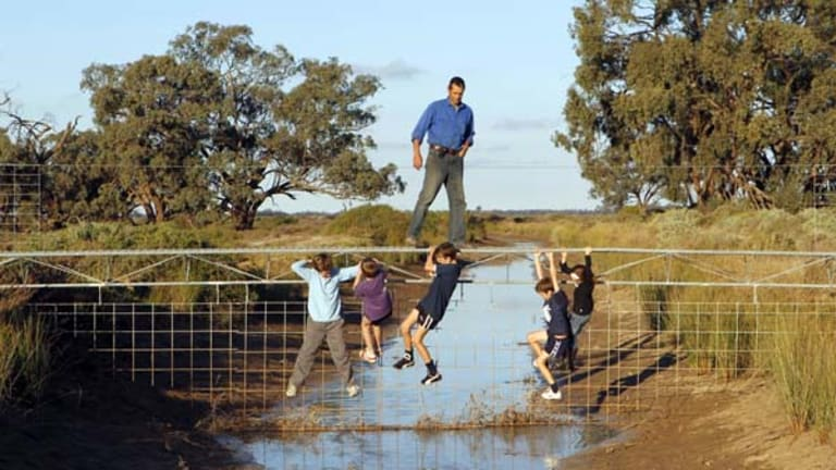 High and dry ... Riverina rice farmer, Jeremy Morton, with some local children. Mr Morton wants to sell his water entitlements,  and close this irrigation channel so he can give up farming.
