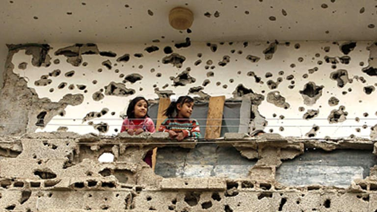Still standing: Palestinian girls look out from the balcony of their home in Rafah that sat in the line of fire during the Israeli offensive in Gaza.