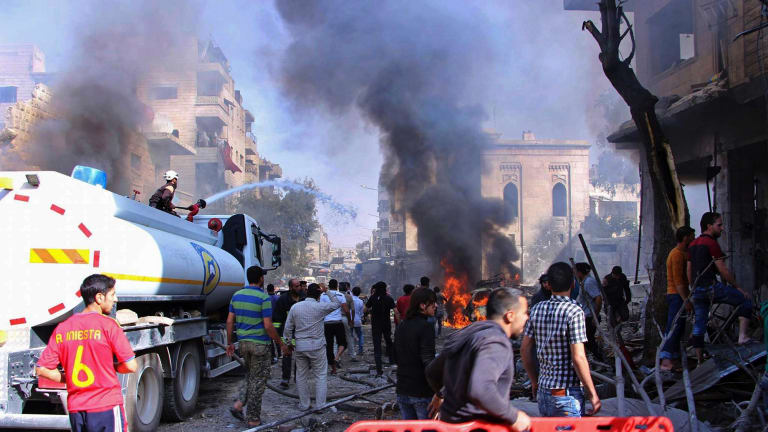 Civil defence workers put out a fire as Syrian citizens gather after an airstrike hit a market in Maaret al-Numan, southern Idlib, Syria, in October.