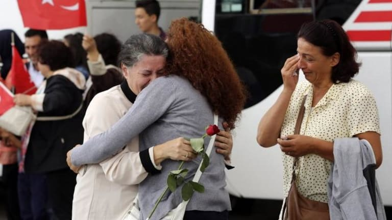 An employee at Turkey's consulate in the northern Iraqi city of Mosul is welcomed by family at Esenboga airport in Ankara, after Turkish intelligence secured the release of more than 40 diplomatic staff held by Islamic State after its capture of the city in June.