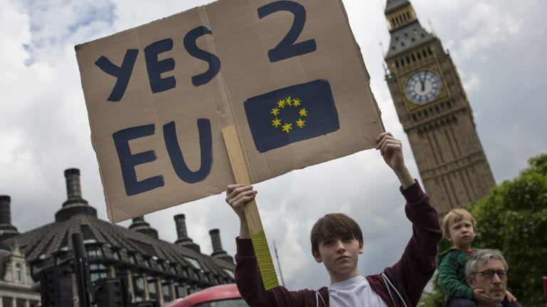 A small group of young people gather to protest on Parliament Square the day after a majority of the British public voted for leaving the European Union.