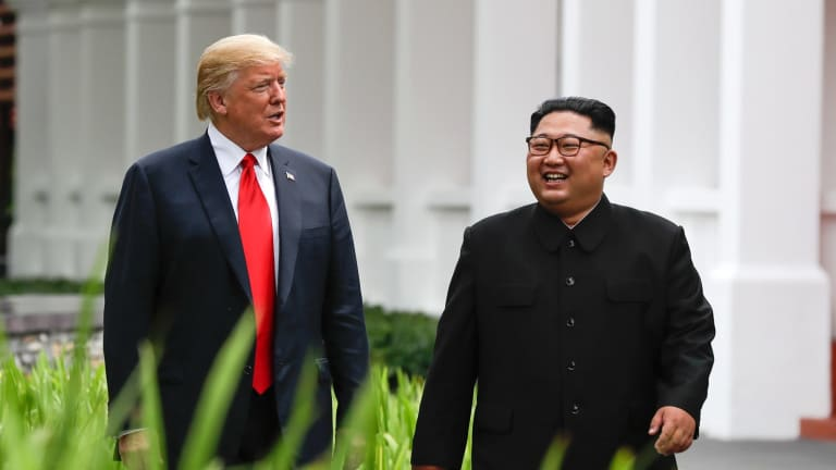 U.S. President Donald Trump and North Korea leader Kim Jong Un walk from their lunch in Singapore.