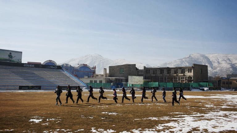 League of their own: The Afghan Women's Cricket team trains on a snow-covered Kabul Cricket Stadium in Afghanistan's capital.