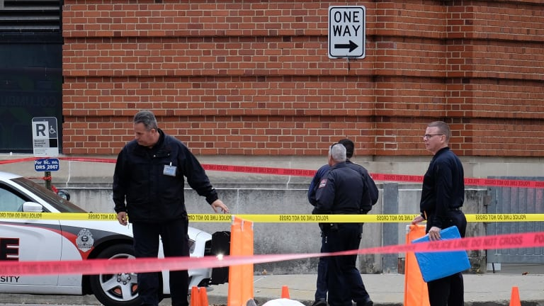 Police cover the body of a suspect outside Watts Hall on the campus of Ohio State University in Columbus, Ohio.