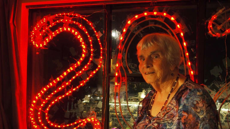 "The ""SOS"" lights shine from Myra's windows, illuminating the residents' plight."