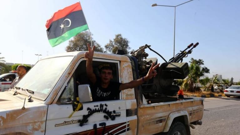 An Islamist fighter from the Fajr Libya coalition flashes the V sign for victory at the entrance of Tripoli international airport after capturing it from Zintan force, allies of rogue general Khalifa Haftar, following many days of clashes.