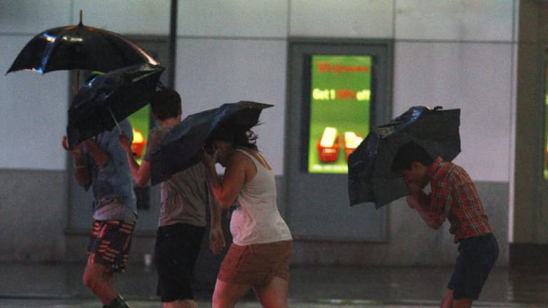 Tourists walk through Times Square as Hurricane Irene arrives in New York.