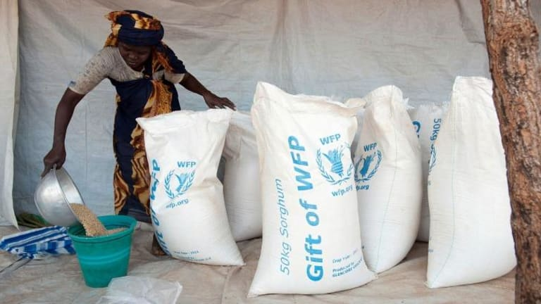 A local aid worker prepares rations of sorghum in May to be distributed to refugees at the Yida refugee camp in Unity State, South Sudan.