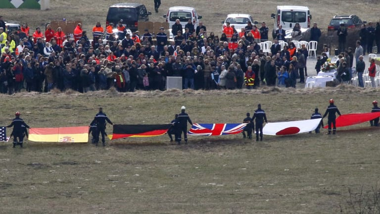 Flags representing some of the nationalities of the victims are seen as family members and relatives gather near the crash site of an Airbus A320 in the French Alps.