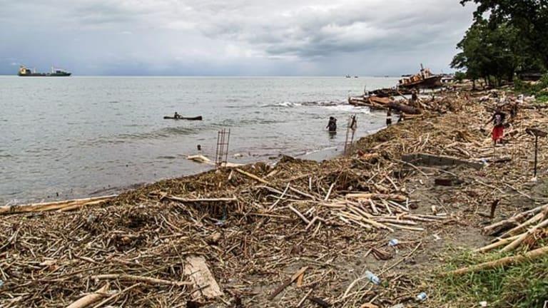 Locals walk amongst debris that was washed ashore near Honiara.