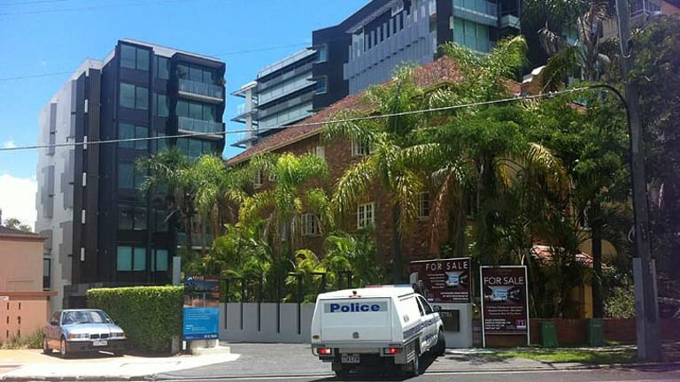 Police outside Hohepa Morehu-Barlow's apartment building, at rear.