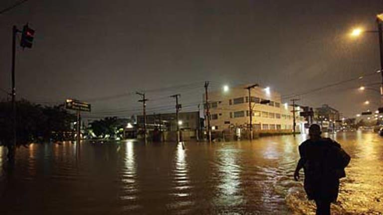 A man walks through a flooded street after heavy rains in Barra Funda, Sao Paulo.