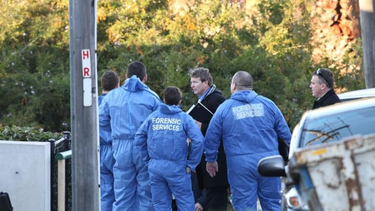 Detectives speak to forensic officers at the scene this morning.