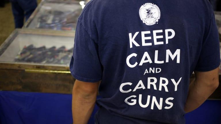 A man attending the Fall 2015 Knob Creek Machine Gun Shoot in West Point, Kentucky, wears a National Rifle Association T-shirt.